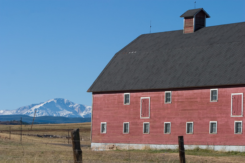 The large peaks of the Rocky Mountains rise behind an old red barn located between Denver and Colorado Springs.