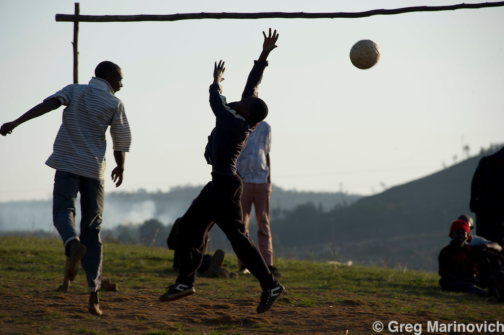 Ngwenya, Swaziland, Sept 3, 2011. Youths play footbll on a rough pitch under the mountain where the old Anglo American iron ore mine in Malalotja National Park used to be.  Photo Greg Marinovich / Storytaxi