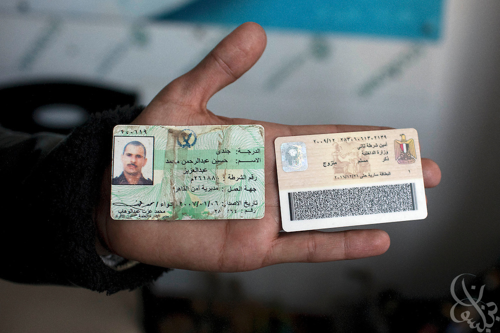 Anti-Mubarak protesters show the identification badge of a policeman they captured during overnight clashes in Tahrir Square February 03, 2011 in Cairo, Egypt.  The protesters claim that many Mubarak supporters attacking them are policemen, or are thugs being paid by the Mubarak regime.  (Photo by Scott Nelson).