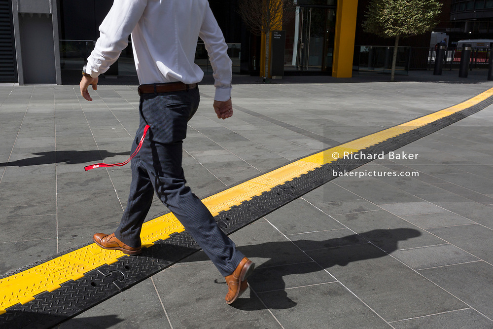 A man crosses a yellow line that covers hazardous electrical cabling at Leadenhall in the City of London, (aka The Square Mile) the capital's financial district, on 2nd September 2019, in London, England.