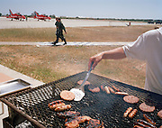 Anonymous chef prepares BBQ burgers and sausages as a pilot of the Red Arrows, Britain's RAF aerobatic team walks past.