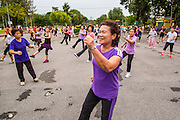 06 OCTOBER 2012 - BANGKOK, THAILAND: A public exercise class in Lumphini Park in Bangkok. Lumphini Park is 142 acre (57.6-hectare) park in Bangkok, Thailand. This park offers rare open public space, trees and playgrounds in the congested Thai capital. It contains an artificial lake where visitors can rent boats. Exercise classes and exercise clubs meet in the park for early morning workouts and paths around the park totalling approximately 1.55 miles (2.5 km) in length are a popular area for joggers. Cycling is only permitted during the day between the times of 5am to 3pm. Smoking is banned throughout smoking ban the park. The park was created in the 1920's and named after Lumbini, the birthplace of the Buddha in Nepal.   PHOTO BY JACK KURTZ