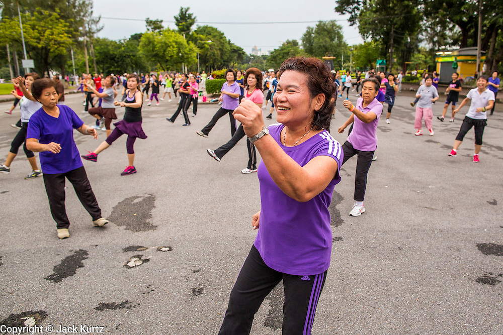 06 OCTOBER 2012 - BANGKOK, THAILAND: A public exercise class in Lumphini Park in Bangkok. Lumphini Park is 142 acre (57.6-hectare) park in Bangkok, Thailand. This park offers rare open public space, trees and playgrounds in the congested Thai capital. It contains an artificial lake where visitors can rent boats. Exercise classes and exercise clubs meet in the park for early morning workouts and paths around the park totalling approximately 1.55 miles (2.5km) in length are a popular area for joggers. Cycling is only permitted during the day between the times of 5am to 3pm. Smoking is banned throughout smoking ban the park. The park was created in the 1920's and named after Lumbini, the birthplace of the Buddha in Nepal.   PHOTO BY JACK KURTZ