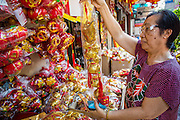 "22 JANUARY 2013 - BANGKOK, THAILAND:   A customer looks at Chinese New Year merchandise on display in a shop on Charoen Krung Road in Bangkok's Chinatown district. Chinese New Year is not an official public holiday in Thailand, but it is one the biggest celebrations in the Bangkok, which has a large Chinese population. Chinese New Year is February 10 this year. It will be the ""Year of the Snake.""    PHOTO BY JACK KURTZ"