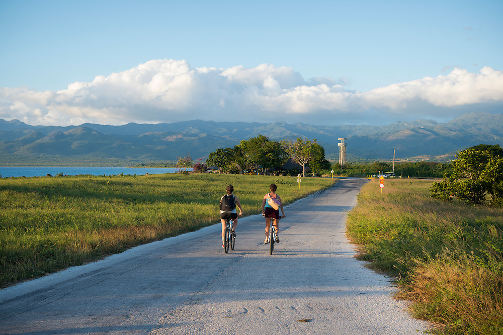Two young women from Spain, traveling in Cuba, ride bicycles at sunset on a two-lane road paralleling the Caribbean Sea between Playa Ancon and Trinidad, Cuba.