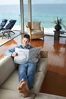 Man lying on sofa reading newspaper elevated view.