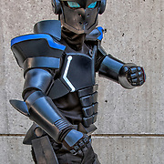Cosplay attendee in their costume, as  Akame ge Kill is a Japanese shōnen manga amime series.<br /> <br />  The story focuses on Tatsumi who is a young villager that travels to the Capital to raise money for his home only to discover a strong corruption in the area. The assassin group known as Night Raid recruits the young man to help them in their fight against the Empire to end its corruption. The series is known for its graphic content. <br /> <br /> Cosplay, a contraction of the words costume play, is a performance art in which participants called cosplayers wear costumes and fashion accessories to represent a specific character.
