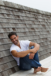 handsome man leaning against a shingled rooftop
