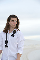 man with long brown hair wearing a tuxedo shirt and loose tie outdoors