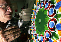 Costa Rican painter Fernando Alpizar, 65, decorates a wheel of a traditional car at the Chaverri Traditional Car Factory in Sarchi, about 50 km  north of San Jose, Costa Rica on Friday November 25, 2005. This kind of painted cars are a symbol of the folk culture in Costa Rica. UNESCO recognize this cars as Humankind Nonmaterial Patrimony.(Photo/Cristobal Herrera).