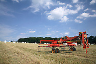 Tedder in hay meadow with large wrapped bales
