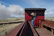 Passengers aboard the Cumbres & Toltec Scenic Railroad as it departs Antonito Depot en route to Chama, New Mexico.