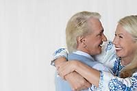 Senior couple embracing in studio head and shoulders