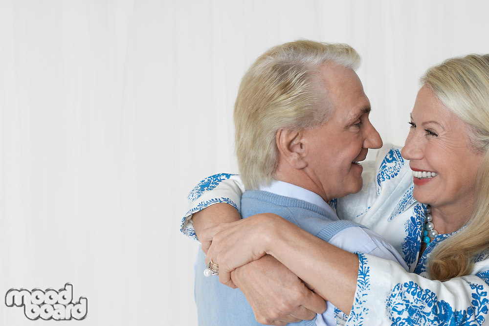 Senior couple embracing in studio head and shoulders
