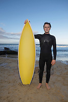 Man holding surfboard standing on beach portrait