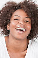 Close-up portrait of joyful African American young woman laughing