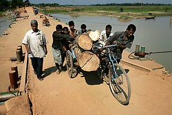 BANGLADESH SYLHET CHHATTAK 24FEB05 - A rikshaw puller and helpers move a rikshaw heavily laden with logs up a ramp near Chhattak Gas Field, close to border with India/Meghalay...jre/Photo by Jiri Rezac ..© Jiri Rezac 2005..Contact: +44 (0) 7050 110 417.Mobile:  +44 (0) 7801 337 683.Office:  +44 (0) 20 8968 9635..Email:   jiri@jirirezac.com.Web:    www.jirirezac.com..© All images Jiri Rezac 2005- All rights reserved.