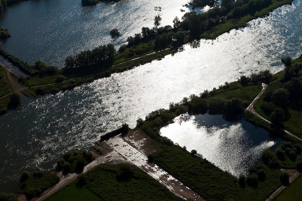 Nederland, Overijssel, Gemeente Olst, 03-10-2010; stuw Olst, restant van de IJssellinie (waterlinie) gebouwd tijdens de Koude Oorlog. Lokatie van de stuw in rivier de IJssel, de betonnen weg vormde de ondergrond van de afsluitbare pijlerdam die uitkwam op het landhoofd (de betonnen muur). Oorspronkelijk stond op beide oevers zo'n landhoofd waartegen, aan de rivierzijde caissons afgezonken konden worden. Hierdoor zou het rivierwater het omliggende land doen overstromen (innunderen). Ook de haven voor de caissons, stroomopwaarts (rechtsonder), is nog aanwezig..Barrage Olst, remnant of the IJssel line (water line) was built during the Cold War. Location of the Barrage in the river IJssel, under the concrete road was the pillar dam, at the end of the road the and abutment (the concrete wall). Originally, such abutments were on both banks and were used to position caissons (on the river side) that subsequently could be sunk. This would make the river flood the surrounding land (inundation). The port for the caissons, upstream (right) is still present...luchtfoto (toeslag), aerial photo (additional fee required).foto/photo Siebe Swart