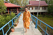 Apr. 3, 2010 - KHUN SAMUTCHINE, THAILAND: Abbot ATHIKARN SOMNUK ATIPANYO, at Wat Samutchine, walks across a cement bridge to the prayer hall at the temple. Rising sea levels brought about by global climate change threaten the future of Khun Samutchine, a tiny fishing village about 90 minutes from Bangkok on the Gulf of Siam. The coastline advances inland here by about 20 metres (65 feet) per year causing families to move and threatening the viability of the village. The only structure in the village that hasn't moved, their Buddhist temple, is completely surrounded by water and more than 2 kilometers from the village. The temple and the village have asked the Thai government and several NGOs for help, but the only help so far is a narrow concrete causeway the government is building that will allow people to walk into the temple from a boat landing two miles away. The walk to the village from a closer boat landing is shorter, but over an unimproved mud flat that is nearly impassible in the rainy season.  PHOTO BY JACK KURTZ