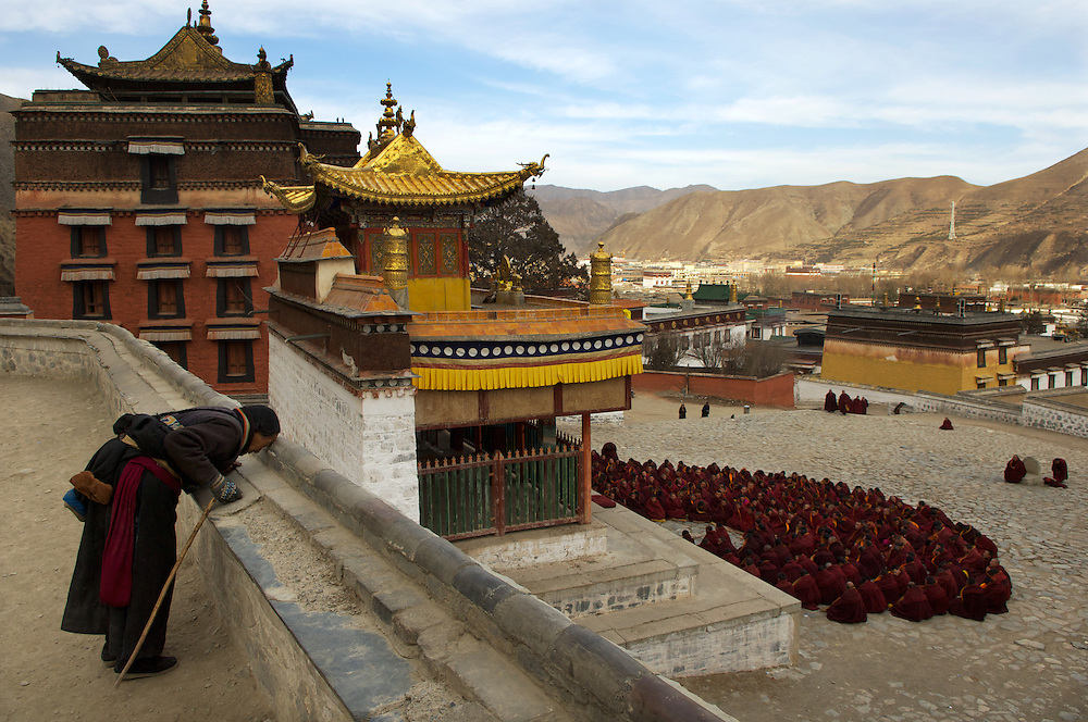 A pilgrim walking the kora pauses for prayer, whilst buddhist monks wearing heavy maroon robes congregate outside the main prayer hall of Labrang Monastery, for Losar prayers, at Tibet's New Year.<br />