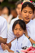 20 OCTOBER 2012 - BANGKOK, THAILAND: A mother and daugher pray for peace in Thailand's violence wracked southern provinces during a special alms giving ceremony in Bangkok. More than 2,600 Buddhist Monks from across Bangkok and thousands of devout Thai Buddhists attended the mass alms giving ceremony in Benjasiri Park in Bangkok Saturday morning. The ceremony was to raise food and cash donations for Buddhist temples in Thailand's violence plagued southern provinces. Because of an ongoing long running insurgency by Muslim separatists many Buddhist monks in Pattani, Narathiwat and Yala, Thailand's three Muslim majority provinces, can't leave their temples without military escorts. Monks have been targeted by Muslim extremists because, in the view of the extremists, they represent the Thai state.        PHOTO BY JACK KURTZ