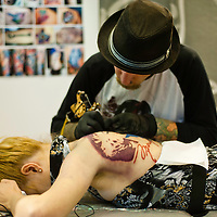 Manchester, UK - 4 August 2012: an artist creates a new tattoo on a girls back during the Manchester Tattoo Show, one of the most popular conventions of the UK tattoo community.