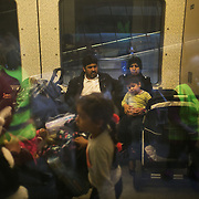 A refugee family on their way to Sweden and safety on a train from Copenhagen. Volunteers can be seen in the reflection. An unprecedented number of refugees arrived from Germany in early September, most being Syrian war refugees, some from Afghanistan. Most wanted to travel on to Sweden and a number of Danish citizens created a spontanious network to assist the refugees with travel, food, clothes and psycological support.