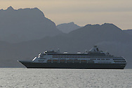 Holland America's Ryndam cruise ship glides past mountains of Baja peninsula near Loreto, Baja Sur, Mexico.