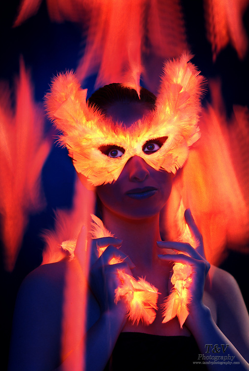 Young woman with a glowing feather mask and feathers in her hand against a motion blue background.Black light
