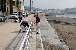 Painting the railings, Aberystwyth promenade, Wales