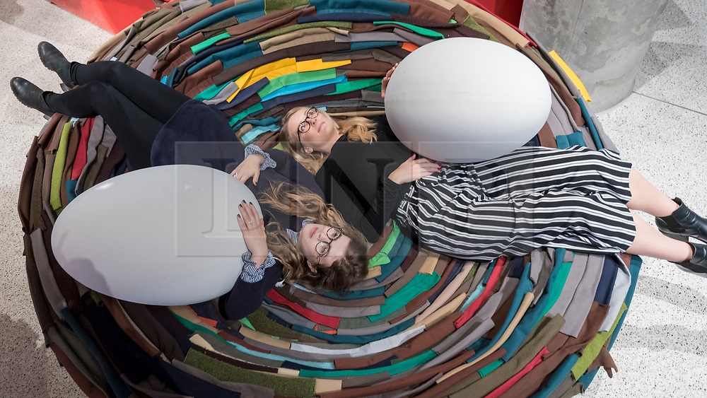 "© Licensed to London News Pictures. 06/11/2018. LONDON, UK. Visitors lay on ""The Nest"", 1973, by Gianni Ruffi.  Preview of ""Home Futures"", at the Design Museum.  The exhibition, in partnership with IKEA Museum Almhult, asks are we living in the way that pioneering architects and designers once predicted, or has our idea of home proved resistant to real change?  More than 150 objects and experiences are on display 7 November to 24 March 2019.  Photo credit: Stephen Chung/LNP"