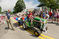 "Mikey Langley drives the John Deere ""family float"" with his brother Jonny and Noelle and Alexis Colarusso riding out back during the 4th of July parade in Gilmanton Wednesday.  (Karen Bobotas/for the Laconia Daily Sun)"