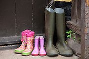 Wellington boots at front door of cottage in Bossington in Exmoor, Somerset, United Kingdom