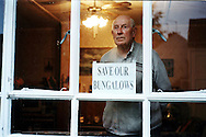 In 2002, the local authorities in Redditch in the Midlands wanted to pull down the 32 Dolphin Road prefabs and redevelop the area. Alan Mason, one of the residents, had seen some of my work published on the internet and wondered if I could use my contacts to alert whoever could help them with their fight against the council. I said I would do what was in my limited power and travelled to Redditch on a stormy day of October 2002. Although it was only about 40 minutes by train from Birmingham, I had the feeling I was reaching an end of the world. Maybe because the tracks were stopping there, it was the end of the line. This photo shows Jack in his prefab in 2002, during the campaign to save the bungalows. Jack was the oldest resident on the estate.