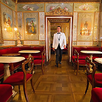 VENICE, ITALY - DECEMBER 02:  A waiter of Caffe Florian  walsk across one of the rooms to check for final details ahead of the daily opening on December 2, 2011 in Venice, Italy.The Venetian coffee houses have a  long standing history, established at the beginning of 1700 around St. Mark Square have been the centre of cultural meeting and innovations for centuries and served customers like Dickens, Goethe, Casanova and Lord Byron. San Marco is one of the six sestieri of Venice, lying in the heart of the city.