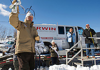 Councilor Armand Bolduc prepares to hand out bibs to riders in Sunday's Open race as the crowd is welcomed by Miss Lakes Region Kendall Wipff, Governor Maggie Hassan and Mayor Ed Engler during Laconia's 85th annual World Championship Sled Dog Derby.  (Karen Bobotas/for the Laconia Daily Sun)