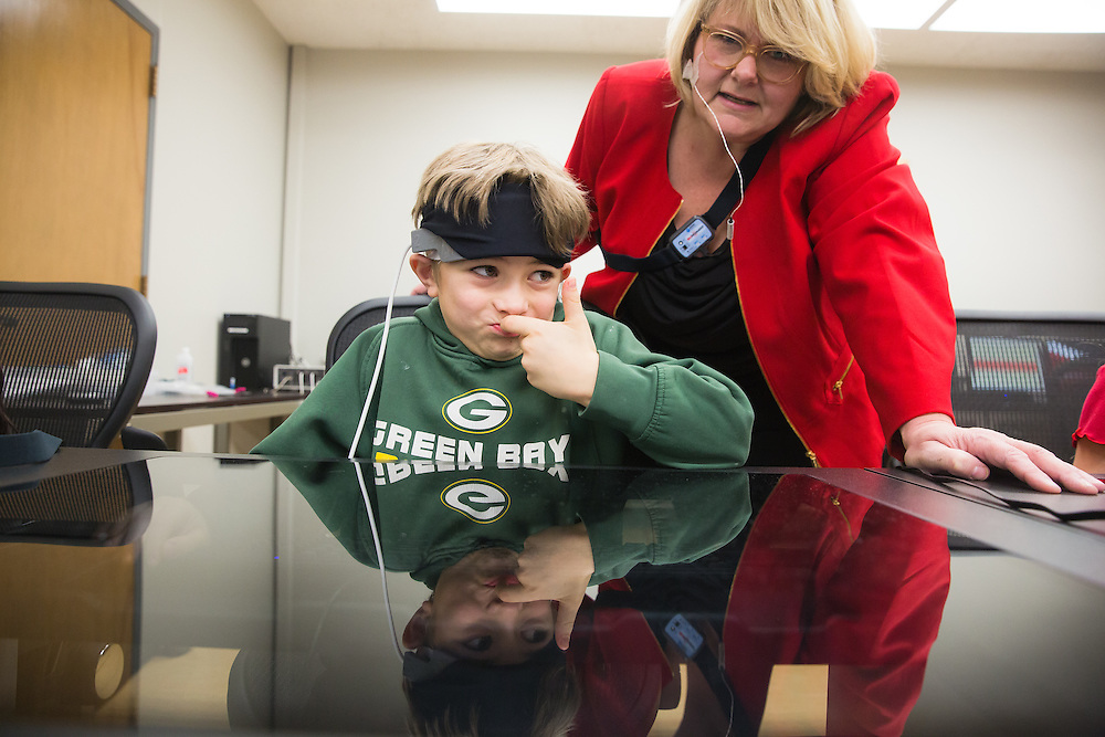 Ramsey Itani, 7, a first-grade student at Sunnyside Elementary in Pullman, Wash., isn't quite sure of his the answer to his teacher's, Laura Grant, questions as he wears a Functional Near Infrared Spectroscopy device during a field trip to the Washington State University neurocognition sciene lab Monday, Feb. 22, 2016.