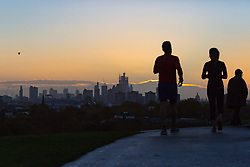 Walkers and runners enjoy the crisp early morning light as day breaks over London's skyline, seen from Primrose Hill, to the north of the city. London, November 13 2018.