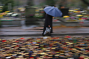 Woman with blue umbrella, blurred in motion. Lodz, Poland cemetery on All Saints Day.