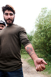 FRANCE GRANDE SYNTHE 2AUG17 - Iraqi Kurd Ryan Salah Jabar, 24, displays his Union Jack and 'London' tattooed on his forearm at the unofficial Jungle II camp near Grande Synthe, Dunkirk, northern France.<br /> <br /> He claims to have worked as a translator for the British Army for 5 years and has been in the camp for 3 months. During that time, he attempted to enter the UK by hanging on to the axles of a truck bound for the ferry port and has been detained and subsequently let go by French police several times.<br /> <br /> jre/Photo by Jiri Rezac<br /> <br /> © Jiri Rezac 2017
