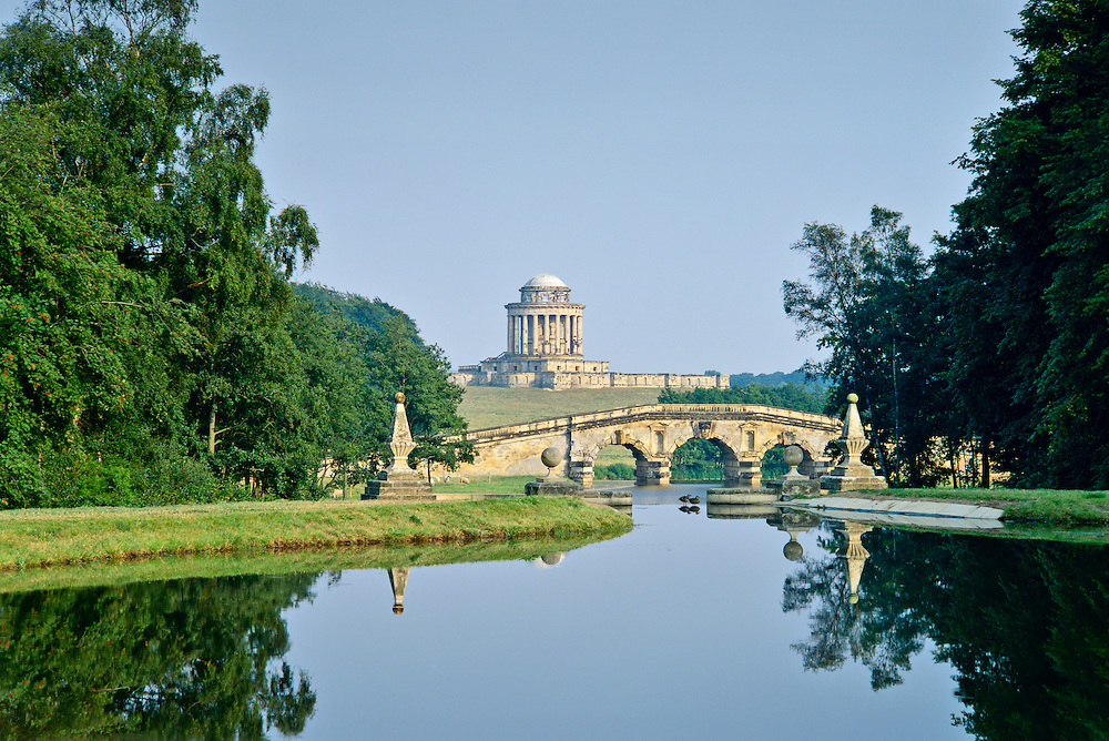 Gardens of Castle Howard stately home, Yorkshire, England. Mausoleum designed by Nicholas Hawksmoor beyond the New River Bridge.