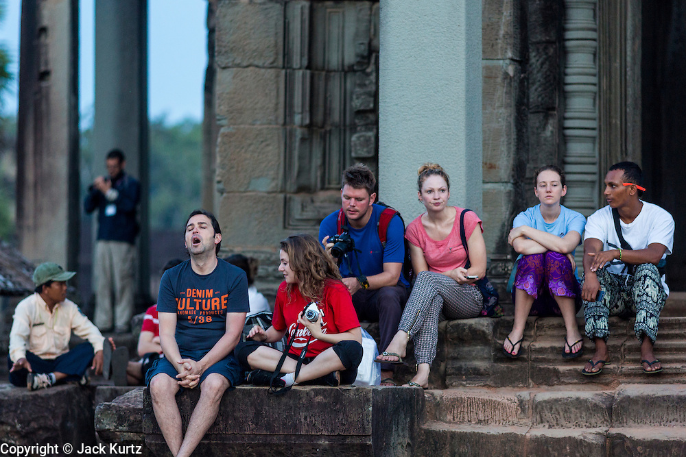 """02 JULY 2013 - ANGKOR WAT, SIEM REAP, SIEM REAP, CAMBODIA:  Tourists wait on the west side of Angkor Wat to see the sunrise from behind the temple. Angkor Wat is the largest temple complex in the world. The temple was built by the Khmer King Suryavarman II in the early 12th century in Yasodharapura (present-day Angkor), the capital of the Khmer Empire, as his state temple and eventual mausoleum. Angkor Wat was dedicated to Vishnu. It is the best-preserved temple at the site, and has remained a religious centre since its foundation– first Hindu, then Buddhist. The temple is at the top of the high classical style of Khmer architecture. It is a symbol of Cambodia, appearing on the national flag, and it is the country's prime attraction for visitors. The temple is admired for the architecture, the extensive bas-reliefs, and for the numerous devatas adorning its walls. The modern name, Angkor Wat, means """"Temple City"""" or """"City of Temples"""" in Khmer; Angkor, meaning """"city"""" or """"capital city"""", is a vernacular form of the word nokor, which comes from the Sanskrit word nagara. Wat is the Khmer word for """"temple grounds"""", derived from the Pali word """"vatta."""" Prior to this time the temple was known as Preah Pisnulok, after the posthumous title of its founder. It is also the name of complex of temples, which includes Bayon and Preah Khan, in the vicinity. It is by far the most visited tourist attraction in Cambodia. More than half of all tourists to Cambodia visit Angkor.         PHOTO BY JACK KURTZ"""