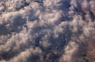 Aerial of snowy winter mountains in the American West, seen through a lacy curtain of clouds