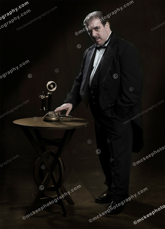 Tycoon,  dressed in 1920's style tuxedo, with old Straight-Shaft Dial Candlestick Automatic Electric telephone