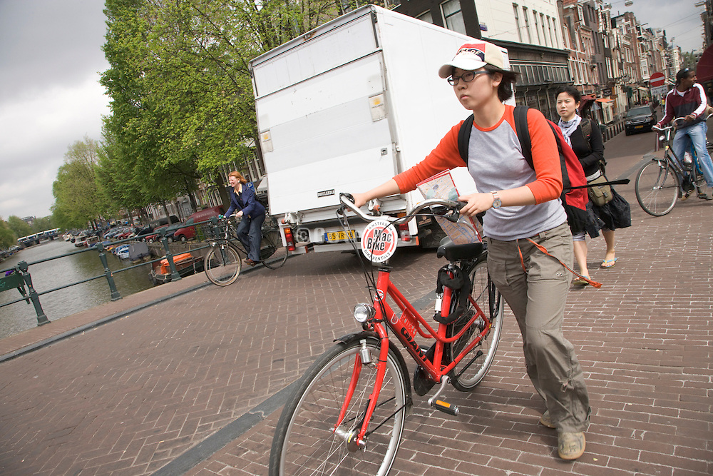 young Asian female with a rented Mac Bike walking across a canal in Amsterdam
