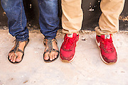 VSO ICS volunteer pair Izak Lees and Nasir Bakari are quite literally walking in each others shoes after swapping footwear. They are preparing for the VSO ICS Community Action Day CAD held for local members of the community in Y2K Hall Lindi, Lindi region. Tanzania.