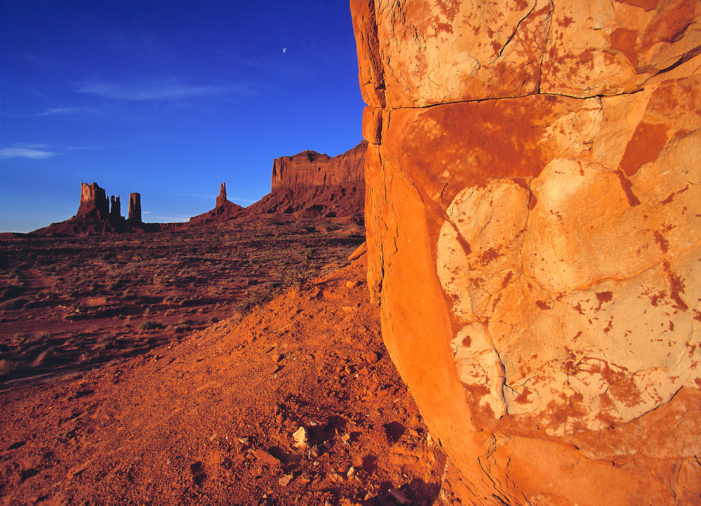 Details in a sandstone boulder contrast with the simple buttes in the distance in Monument Valley, Utah.