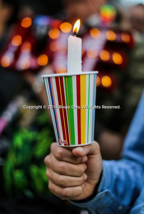 6月13日,在美国洛杉矶市政大楼外,一名民众手举蜡烛参加悼念活动。当日,美国洛杉矶举行烛光守夜活动,数千民众参加悼念周日发生在美国佛罗里达州奥兰多市一家夜总会的枪击事件遇难者。新华社发 (赵汉荣摄)<br /> Several thousand people attend a candlelight vigil at Los Angeles City Hall for the victims of Sunday's Orlando nightclub shooting massacre, in Los Angeles, California, the United States, on Monday, June 13, 2016. (Xinhua/Zhao Hanrong)(Photo by Ringo Chiu/PHOTOFORMULA.com)<br /> <br /> Usage Notes: This content is intended for editorial use only. For other uses, additional clearances may be required.