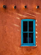 A turquoise-painted window in an adobe wall with vigas. This is the quintessential look of traditional New Mexico architecture.
