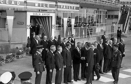 President John F. Kennedy arrives at Dublin Airport.  Kennedy replies to President de Valera's speech of welcome.  Onlookers include President Kennedy's sisters, Mrs. Eunice Shriver and Mrs. Jean Smith; An Taoiseach Seán Lemass; An Tanaiste Mr. McAntee; Dr. Ryan, Minister for Finance, and Mr. Frank Aiken, Minister for External Affairs..26.06.1963